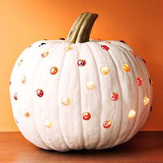 This is clever -- hollow out a pumpkin and drill holes through the flesh. Push a colored marble snugly into each hole, then illuminate with an electronic candle.