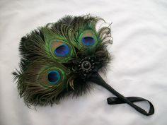 Black Peacock Feather Bridal Fan Order Now from www.indigodaisyweddings.co.uk Specialising in stunning bespoke cocktail fascinators and formal hats in a wide range of colours, perfect for Royal Ascot and The Kentucky Derby. Plus all your wedding floral accessories including shoe clips, bandeau veils,vintage flapper bands, feather and flower fascinators, feather fans, fairy wands, wrist corsages, wedding bouquets & buttonholes. Worldwide Delivery. #wedding #fascinator #indigodaisy #ascot #hea