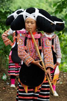 China | Changjiao Miao woman wearing traditional costume and playing a bamboo flute. Guizhou Province | ©Bruno Morandi