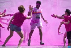 UNITED KINGDOM, London: Volunteers throw colourful powder on a participants taking part in the Colour Run around Wembley Stadium in London on June 1, 2014. AFP PHOTO / JUSTIN TALLIS
