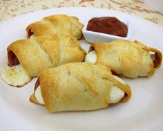 Pepperoni Rolls made with Crescent Rolls, string cheese sticks & pepperoni. Serve with a side of pizza sauce! I'm making these for hors d'oeuvres to take to a party!