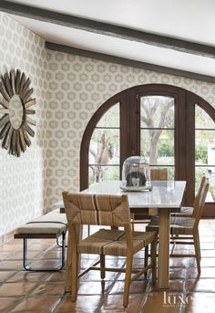 Spanish Colonial Neutral Breakfast Area with Patterned Wallpaper - A bench from One Kings Lane and chairs from Serena & Lily pull up to a marble-topped table from Crate & Barrel in the kitchen's casual dining area.