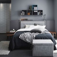 A grey bedroom with a grey ÅRVIKSAND divan bed, a grey TUSENSKÖNA bed spread and a grey FJÄRA storage box.