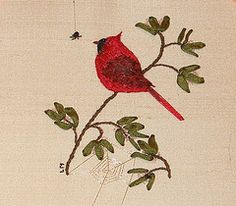 This is a sample of Stumpwork or dimensional embroidery. The cardinal is padded and then stitched using long and short stitch. The leaves are stitched using ribbon embroidery and all of it is stitched on a small piece of silk.