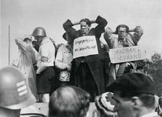 "Danes who had helped the Gestapo during the occupation are driven through the streets on open vans for public humiliation after being arrested by the resistance. The signs says ""Fangeplager fra Shellhuset"" and ""Sandbæk, Plageaand"""
