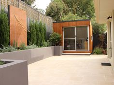 Courtyard garden with Allaro limestone paving, rendered retaining wall, office studio and corten steel screen. The screen will have an east-facing sun-dial (which is currently under construction).