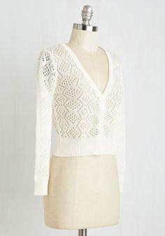 Settle into a corner booth at your favorite coffee shop with a good book, café au lait, and this creamy, cropped cardigan. Sheer and open-knit, it adds the perfect amount of lightweight coziness to any ensemble. Its neutral hue, ribbed hem and sleeves, and deep V-neck make it as indispensable to your daily routine as your morning java. Worn unbuttoned over a floral boho dress with espresso-tinged flats, you're the crème de la crème in this comfy cardi.