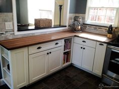 Butcher block countertops, dark floors, white cupboards.