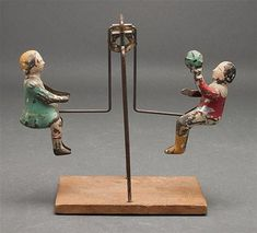 German painted tin seesaw toy, mounted on wood base  early 20th century Estimated Price: 60 - 90