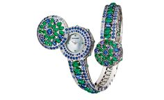 Boucheron Capriccioli watch bracelet paved with blue and purple round cabochon sapphires, oval cabochon emeralds, blue and purple sapphires and diamonds, on white gold. A watch is hidden under the large pattern of the bracelet.