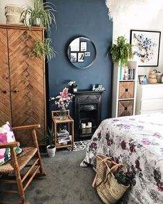 Dark blue chimney breast with black iron fireplace in the bedroom. Pink floral bedding and plenty of plants make this boho chic! Dark Blue Bedrooms, Dark Wood Bedroom, Bedroom Fireplace, Bedroom Black, Dark Furniture Bedroom, Blue And Pink Bedroom, Dark Blue Walls, Dark Blue Living Room, Fake Fireplace