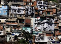 "Giant photographs of women cover the walls of homes in Providencia slum in Rio de Janeiro, Friday, Aug. 15, 2008. A French photographer who identifies himself as JR is exhibiting portraits of women whose loved ones were killed by police as part of his project entitled ""Women are Heroes."""
