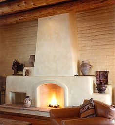 Rumford fireplace set against exposed adobe walls finished with lime paint