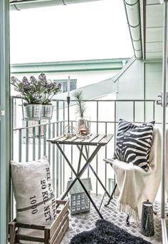 balkon gestalten balkonmöbel geländer klappstühle tisch wolldecke kissen zebra print holzkisten vintage stil