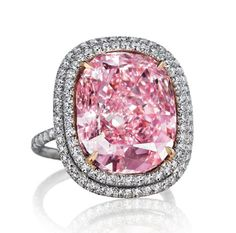 Set with a cushion-shaped fancy vivid pink diamond, weighing approximately 16.08 carats, within a diamond twin surround, to the pink diamond gallery and diamond-set hoop, ring size 6, mounted in platinum and gold Accompanied by report no. 5101646581 dated 18 December 2014 from the GIA Gemological Institute of America stating that the diamond is Fancy Vivid Pink colour, VVS2 clarity, and a Diamond Classification Letter indicating that the diamond had been determined to be Type IIa.