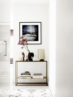 Console table in hallway styled with large flowering branch