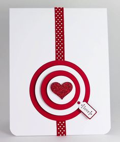"""A glittery red heart is the bullseye on this handmade valentines card.  Red ribbon with white polka dots leads to bigger concentric circles in red and white, with a tiny """"love"""" tag."""