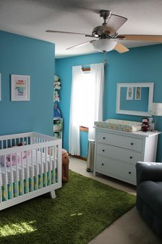 Go bold in the nursery with bright turquoise walls and a fun shaggy green rug.