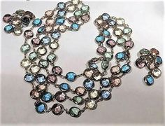 Item # 021708 (B-87)   This is a stunning unsigned Austrian crystal Swarovski necklace and matching clip on earrings demi parure.   The crystals are beautiful pastel colors, yellow, pink, green, blue, turquoise and purple.   Crystals measure 12mm and have been bezel set.   Necklace is extra long at 56 with no clasp.   Clip on earrings are a drop dangle chandelier style measuring 2 on the drop and are 1 at their widest.   Very good vintage condition with typical wear due to age and handling…