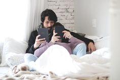 Foto clean em tons claros e bem iluminada com clima aconchegante de outono/inverno. Casal (Melina Souza e Beni) sentados na cama cheia de cobertas, travesseiros e almofadas lendo com kobo (e-reader).