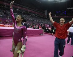 U.S. gymnast Gabrielle Douglas waves to the audience after her final and deciding performance on the floor, followed by coach Liang Chow during the gymnastics women's individual all-around competition.