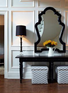 The floors of this home were stained with a custom blend of walnut and dark oak stain to let the grain of the white oak shine through. The walls have all been paneled and painted a crisp white to set off the stark gray used on the upper part. A large black stained console was used with tall glass buffet lamps and an oversized sculptural mirror set above the wall paneling.