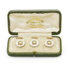 A SET OF FABERGÉ VARICOLOR GOLD AND GUILLOCHÉ ENAMEL SHIRT STUDS, MOSCOW, 1898-1908 comprising three circular studs and backs, each centered with a varicolor gold ribbon-tied wreath set against a ground enameled oyster over a sunburst guilloché ground, struck with Cyrillic initials KF, 56 standard, contained in leather-bound fitted case of London retailer Noble & Co.
