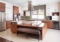 Comptoir et îlot en marbre avec un partie en bois, des armoires en bois et une hotte et des électros en inox