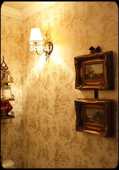 And there's more!  Toile wallpaper, gilt-framed landscapes, either antiques or reproductions, that little sconce lamp.  It's delicious.