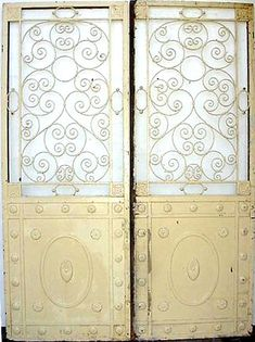 Great pair of 1920s decorative elevator doors from an upscale Madison Avenue, New York City hotel.  Steel and cast iron construction with decorative top panels and steel lowers with decorative cast iron rosettes.  Doors are in good condition considering age, but exhibit some paint loss and minor knicks.  The overall construction is solid, and the doors display rather well.  Several pairs available.  Since we've sold these doors our clients have used them as garden gates, wine cellar doors…