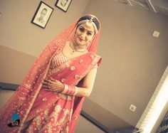 carrot pink lehenga, gold scattered motifs, gold zigzag design, double dupatta, red and white chooda, gold jewelry