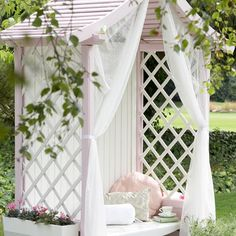 This garden decorating idea is perfect for our rainy summers! A pastel pink paint shade adds a decorative feel to this pretty but practical arbour.