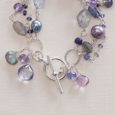 The cool hues of these precious gems lure you into their gaze.   Blue topaz, labradorite, amethyst, iolite, freshwater pearl, and pink quartz create a delicate combination around your wrist. Expertly hand wrapped with dangles and silver sequins, youll love the quality and feel of this one of a kind beauty.  A silver toggle completes this bracelet. Fits a 6 1/2 wrist. Additional sizes are available. Please Convo with questions.  *^*^*^*^*^*^*^*^*^*^*^*^*^*^*^*^*^*^*^*^*^*^*^*^*^*^*^*^*^*^...