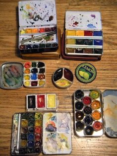 I have lots of purchased ones..but I also make my own. The two in the middle and the bottom right are made in mint tins. I used sculpey (oven bake clay) and made the dividers for the pigments..the bottom right one has cups I repurposed from a dollar store kid's poster paint set and glued in the tin then squeezed in my own tube watercolors...any lidded tin is fair game!