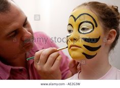 Download this stock image: Girl having her face painted in the design of a bumble bee - AE2G3W from Alamy's library of millions of high resolution stock photos, illustrations and vectors.