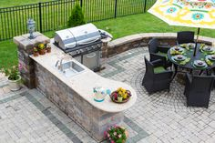 Stylish outdoor backyard kitchen, gas barbecue and dining table set for entertaining guests with formal place settings and flowers on a paved patio