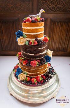 Naked wedding cake with fresh fruit and handmade models
