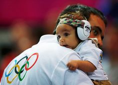 24 hours: London, England: A fan carrying his baby watches the men's handball