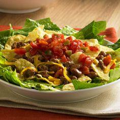 Sencilla Ensalada de Taco... La ensalada de taco se prepara rápidamente con lechuga crujiente cubierta con carne de res molida condimentada, frijoles, queso, nachos y sabrosos tomates