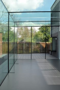 Frameless Glass Box Extension with Glass Fins and Beams to Sky House Showroom - The Courtyard