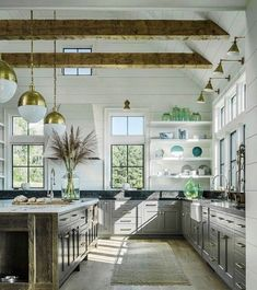 Large modern farmhouse kitchen with white shiplap walls, gray lower cabinets, brass and glass globe pendant lights, and exposed wood beams in the ceiling - Modern Vintage Kitchen Ideas #vintagekitchen