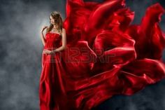 red dress: Красивая женщина в красном шелковом платье, размахивая, как пламя. Глядя вниз. Фото со стока