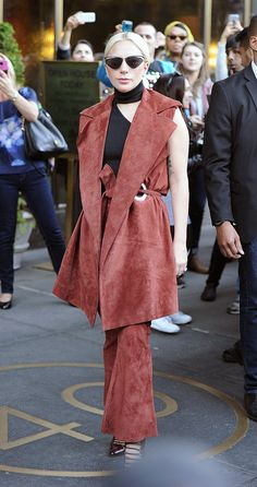 Lady Gaga wears a Beaufille sleeveless suede coat, coordinating flared trousers, and multi-strap Mary Janes