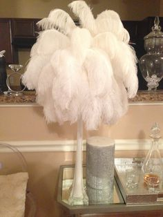 White Ostrich feather / eiffel tower vase centerpieces featuring 45-50 12-14 and 14-16inch ostrich plumes on a 22in eiffel tower vase. Vases available in clear or white.