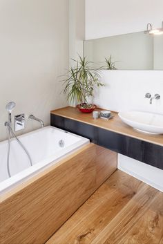 Love the bath shape and the use of timber down the side of the bath and on the vanity top. Also a huge fan of the bowl style sink and taps out of the wall.