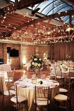 Indoor winter wedding reception with twinkly lights and classic wedding decor. Loft on Lake Weddings--brick and warm oak timber, 20-foot ceilings, and a 65-foot long skylight, what is there to not love?