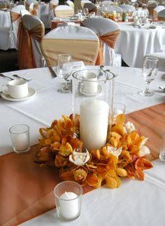 Centro de mesa con flores de tela o de papel fijadas en un plato y una vela grande