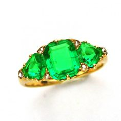 A Victorian three-stone emerald ring, the central emerald-cut emerald, estimated to weigh 1.4 carats, a pear-shaped emerald set to either side, estimated to weigh 1.25 carats for the pair, two rose-cut diamonds set inbetween each stone and one set to each shoulder, all claw-set to an ornate carved yellow gold gallery, to a tapered D-section yellow gold shank, gross weight 4.2 grams, circa 1860