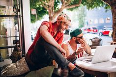 Two best friends sit and laugh at an outdoor cafe by wolfpackcreative | Stocksy United