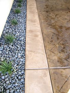 "Omaha tan davis concrete color and bark brown stain. 18""x18"" Roman slate tile. 16"" Border not stained. Mexican Beach pebble and mondo grass. Located in Hertigae Lakes"